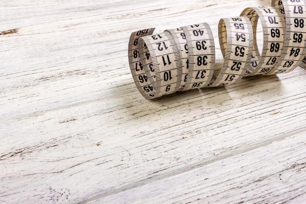 Medidor de indumentária e tesoura na superfície de madeira velha