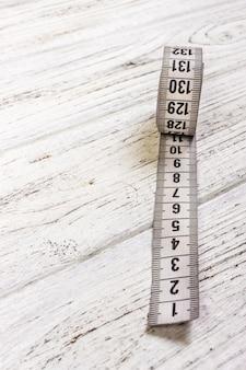 Medidor de indumentária e tesoura no velho de madeira