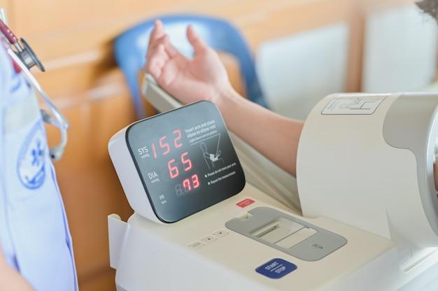 Medidor de pressão arterial mostra hipertensão ou pressão alta, verificação da pressão arterial do paciente no hospital, foco seletivo