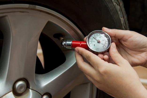 Medidor de pressão de pneu: mão segurando o manômetro de pressão, verificação de pressão de ar para pneu de carro. direção segura.