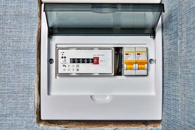 Medidor eletrônico de energia residencial monofásico dentro do quadro de distribuição com disjuntores elétricos.