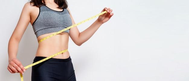 Medindo a cintura com uma fita. mulher apta e saudável em cinza isolado