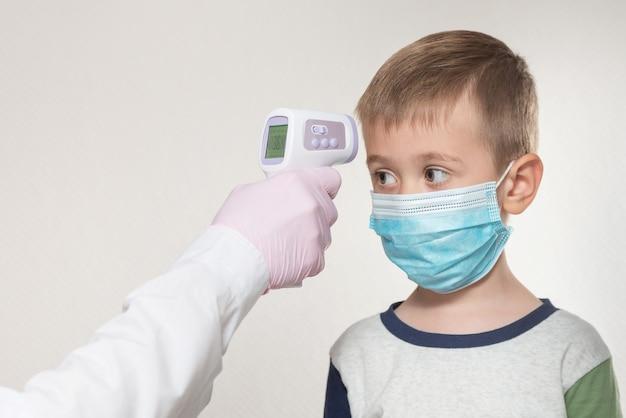 Medindo a temperatura da criança com um termômetro infravermelho