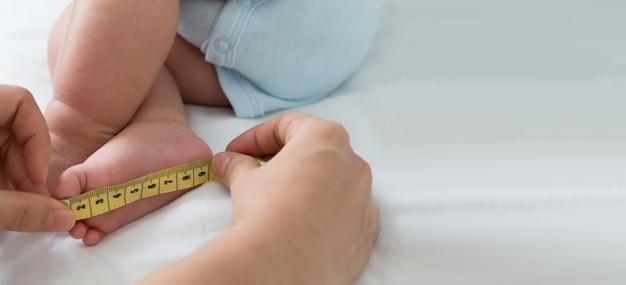 Medindo o tamanho do pé do bebê. três meses de idade