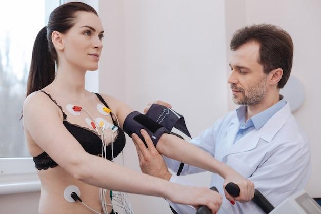 Medindo tudo cardiologista proeminente curioso inventivo que emprega vários itens de equipamento médico para receber um resultado abrangente ao fazer um checkup