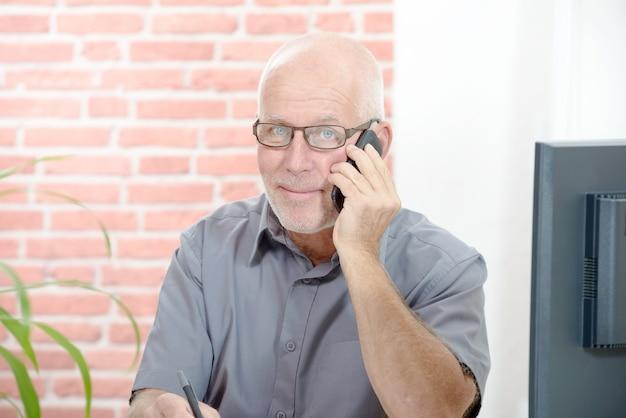 Médio empresário envelhecido sentado na mesa com telefone