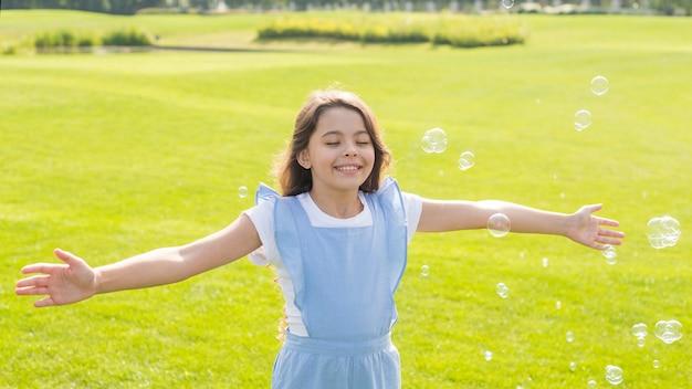 Médio, tiro, alegre, menina, tocando, com, bolhas sabão