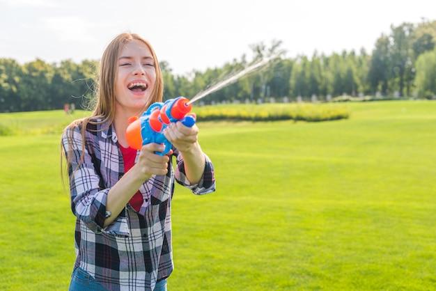 Médio, tiro, alegre, menina, tocando, com, cano de água