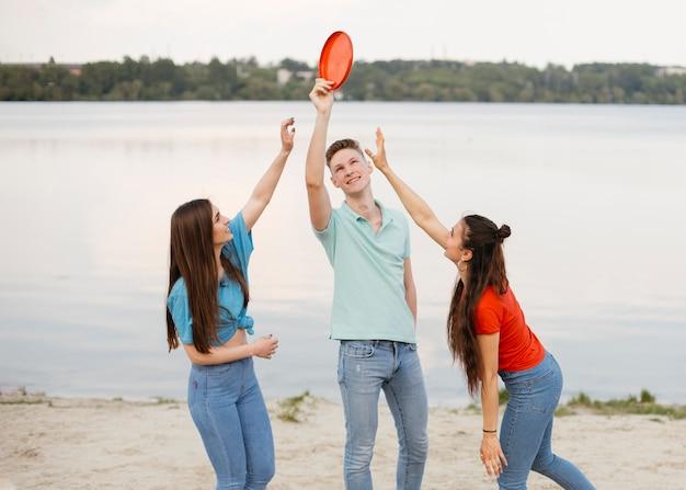 Médio, tiro, amigos, tocando, com, frisbee