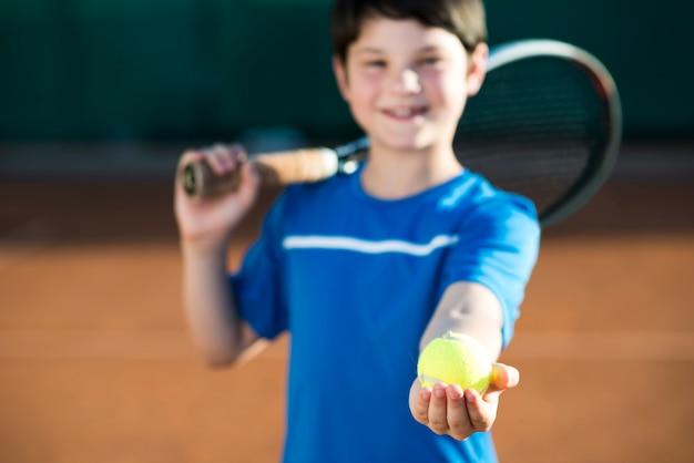 Médio, tiro, criança, segurando, um, bola tênis, em, mão