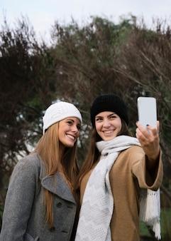 Médio, tiro, dois, sorrindo, mulheres, levando, um, selfie