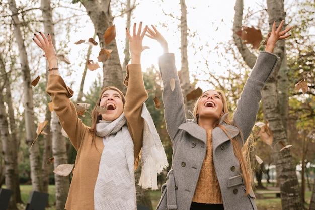 Médio, tiro, duas mulheres, tocando, com, folhas, parque