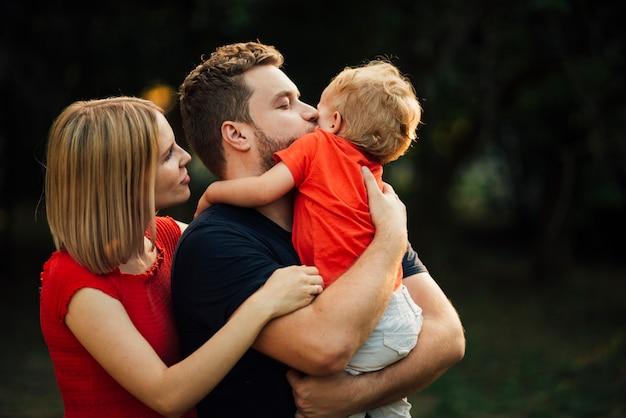 Médio, tiro, feliz, família, beijando, seu, filho