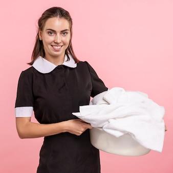 Médio, tiro, feliz, mulher, segurando, lavanderia, cesta