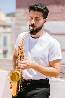 Médio, tiro, frente, vista, músico, tocando, saxofone