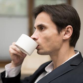 Médio, tiro, homem, bebendo, café