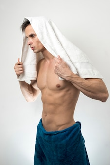 Médio, tiro, homem, posar, com, banhar-se toalha, ligado, cabeça