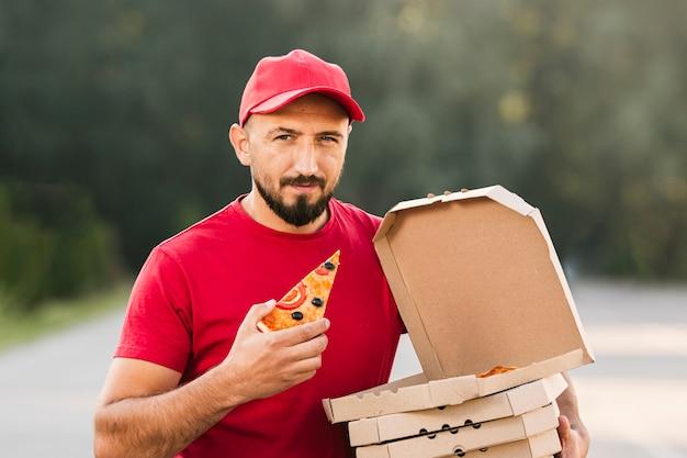 Médio, tiro, homem, segurando, fatia pizza