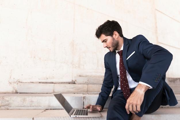 Médio, tiro, homem, sentando, ligado, escadas, com, laptop