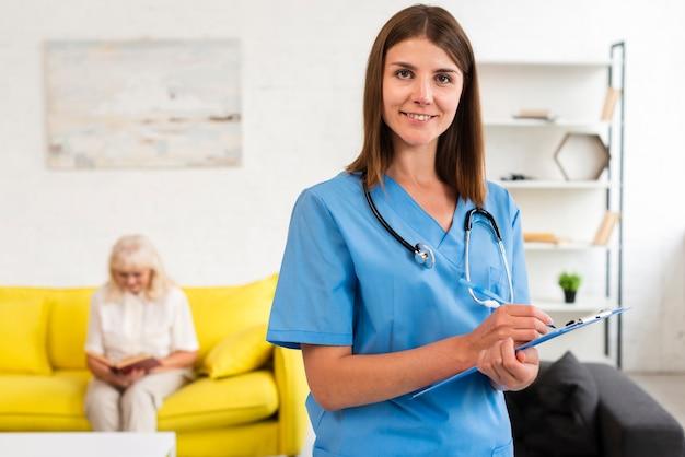 Médio, tiro, médico feminino, com, azul, área de transferência, olhando câmera