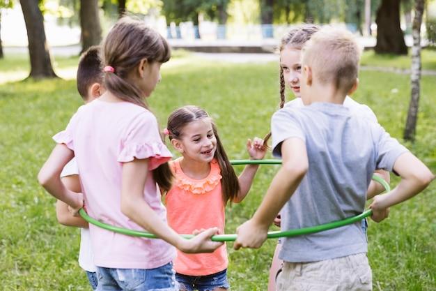 Médio, tiro, melhores amigos, tocando, com, hula hoop