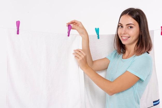 Médio, tiro, mulher, afixando, toalha, com, clothes-pin