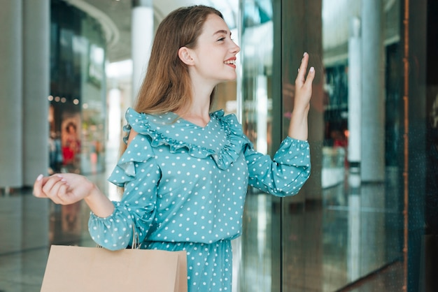 Médio, tiro, mulher, em, centro comercial, waving