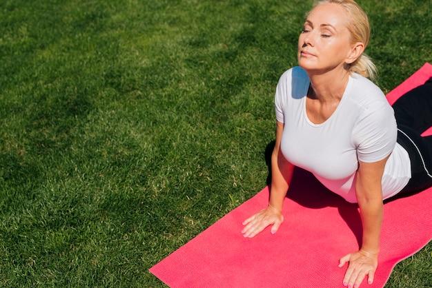 Médio, tiro, mulher, em, ioga posa, ao ar livre