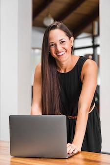Médio, tiro, mulher, sorrindo, e, trabalhando, em, a, laptop