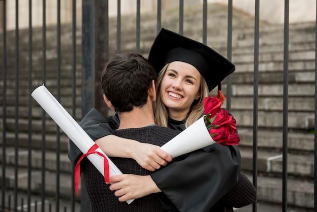 Médio, tiro, par abraçando, em, graduação