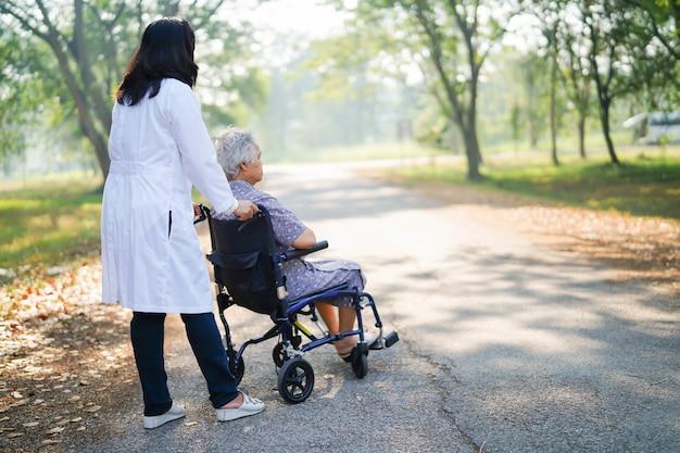 Medique a ajuda e cuide do paciente sênior asiático da mulher que senta-se na cadeira de rodas no parque.