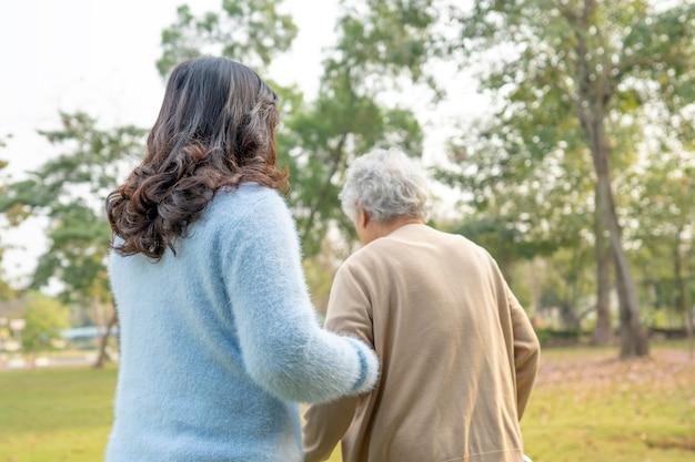Medique a ajuda e o cuidado a mulher sênior asiática do uso walker no parque.