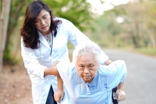 Medique a ajuda e o cuidado paciente sênior asiático da mulher que senta-se na cadeira de rodas no parque.