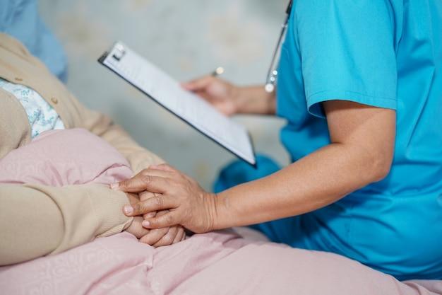 Medique a fala sobre o diagnóstico e a nota na prancheta com o paciente da mulher no hospital.