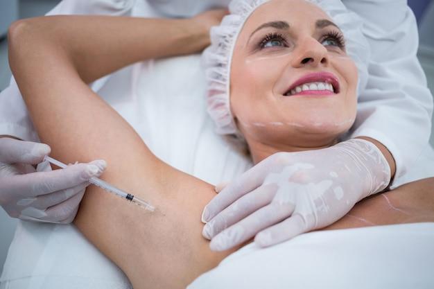 Medique a injeção da mulher em seus poços do braço