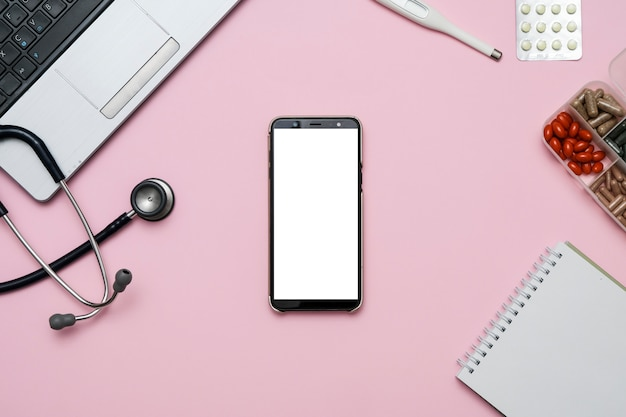 Medique a mesa cor-de-rosa da mesa com smartphone em branco, estetoscópio, medicamento, caderno.