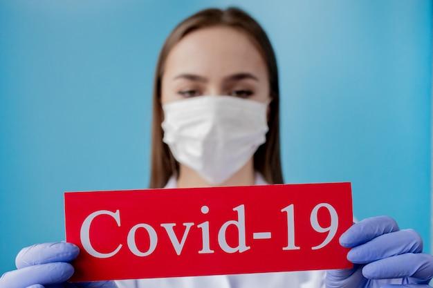 Medique a mulher com máscara cirúrgica que aponta ao papel vermelho com coronavirus do mesaage no fundo azul. organização mundial da saúde (oms) introduziu novo nome oficial para a doença de coronavírus chamado covid-19