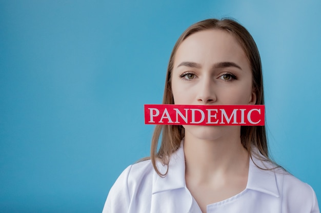 Medique a mulher que aponta ao papel vermelho com coronavirus do mesaage no fundo azul. organização mundial da saúde (oms) introduziu novo nome oficial para a doença de coronavírus chamado covid-19