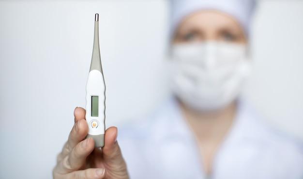 Medique a mulher que veste a máscara protetora médica que mostra um fundo médico do branco do termômetro.