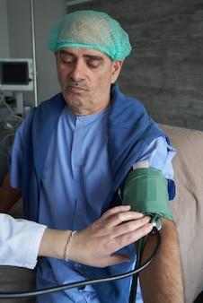 Medique a verificação da pressão sanguínea arterial paciente do homem idoso, close-up
