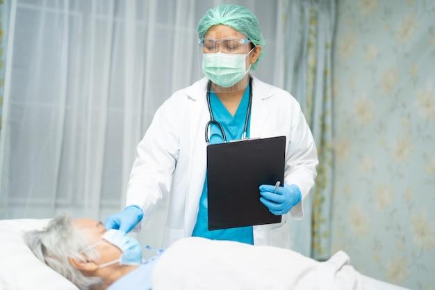 Medique a verificação do paciente sênior asiático da mulher que veste uma máscara protetora no hospital para proteger o vírus covid-19.