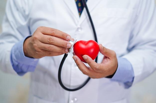 Medique guardar o estetoscópio e o coração vermelho em sua mão no hospital.
