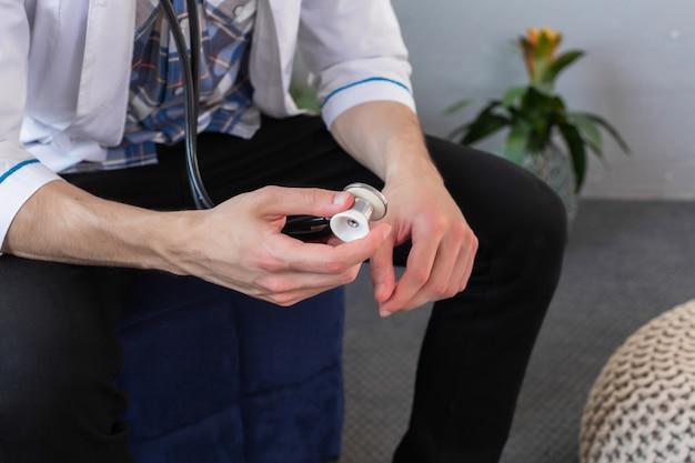 Medique guardar o estetoscópio em sua mão que veste o vestido médico, pronto para examinar um paciente. fechar-se