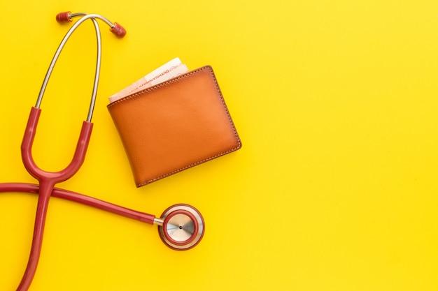 Medique o estetoscópio e a nova carteira de couro dos homens marrons no amarelo. orçamento para verificação de saúde ou dinheiro e conceito financeiro