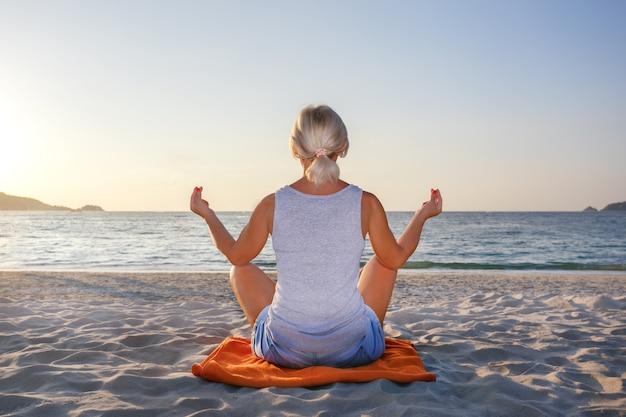 Meditação da mulher em uma pose de ioga na praia.