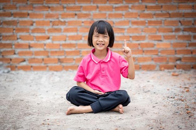 Meditação de assento da criança feliz na terra no fundo da parede de tijolo.