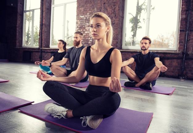 Meditação de ioga de jovens relaxados em pose de lótus na academia