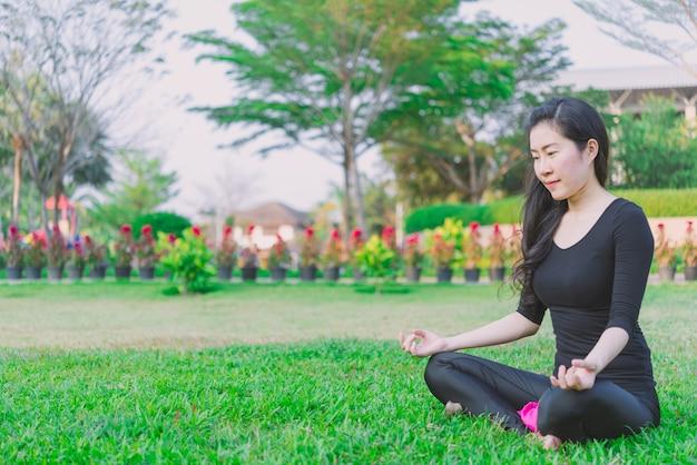 Meditação de manhã mulher praticando na natureza no parque. conceito de estilo de vida de saúde.