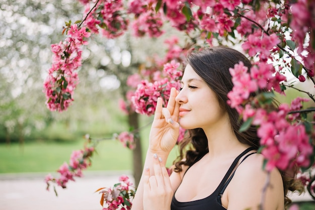 Meditação de mulher bonita com mudra gesto perto de árvore no jardim