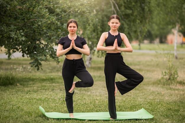 Meditação esportiva de duas jovens no parque